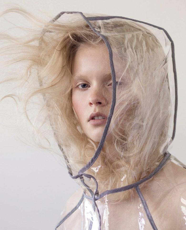 Blond model wearing a clear raincoat