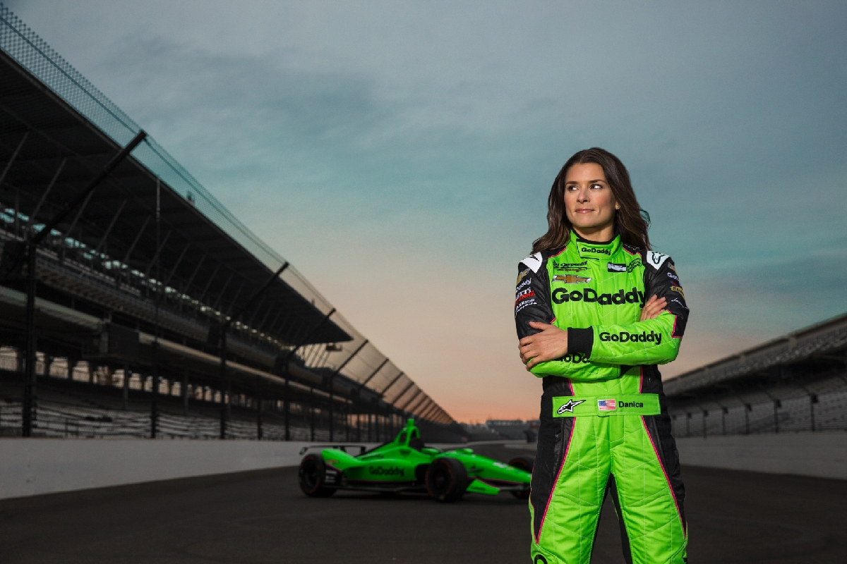 Danica Patrick standing on race track in race car gear