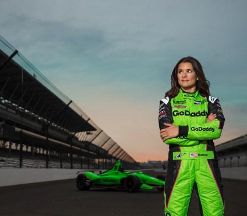 Danica Patrick standing on race track in race car gear