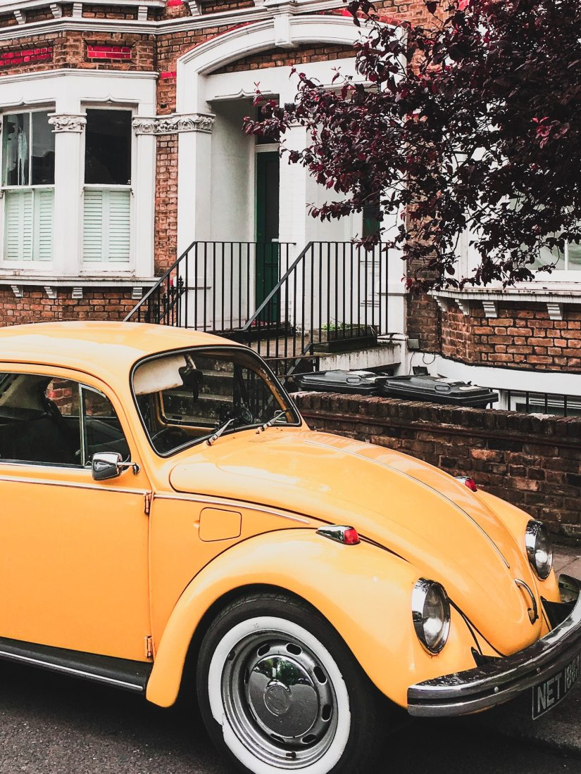 Yellow VW Beetle Parked by the Curb Next to a House