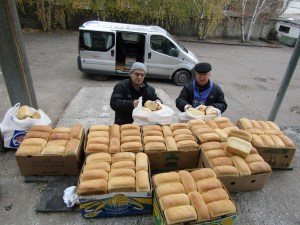 Pastor Gennadiy distributing loaves in grey zone