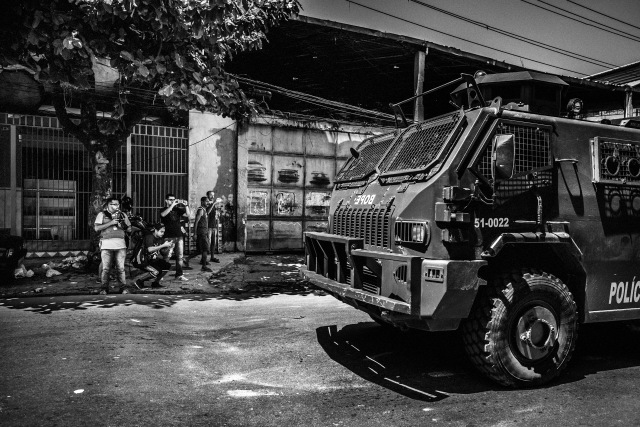 February 2015 - Rio de Janeiro, Brazil: Papo Reto collective members taking pictures and recording videos of the Special Police Forces (BOPE) tank-car patrolling in the streets of Vila Aliança, a favela near Complexo do Alemao. After a militar police cop kill a mototaxi driver in the streets of the favela, several cars and high caliber armed cops invaded the streets in alert of a possible confrontation with the gangs and from the population.