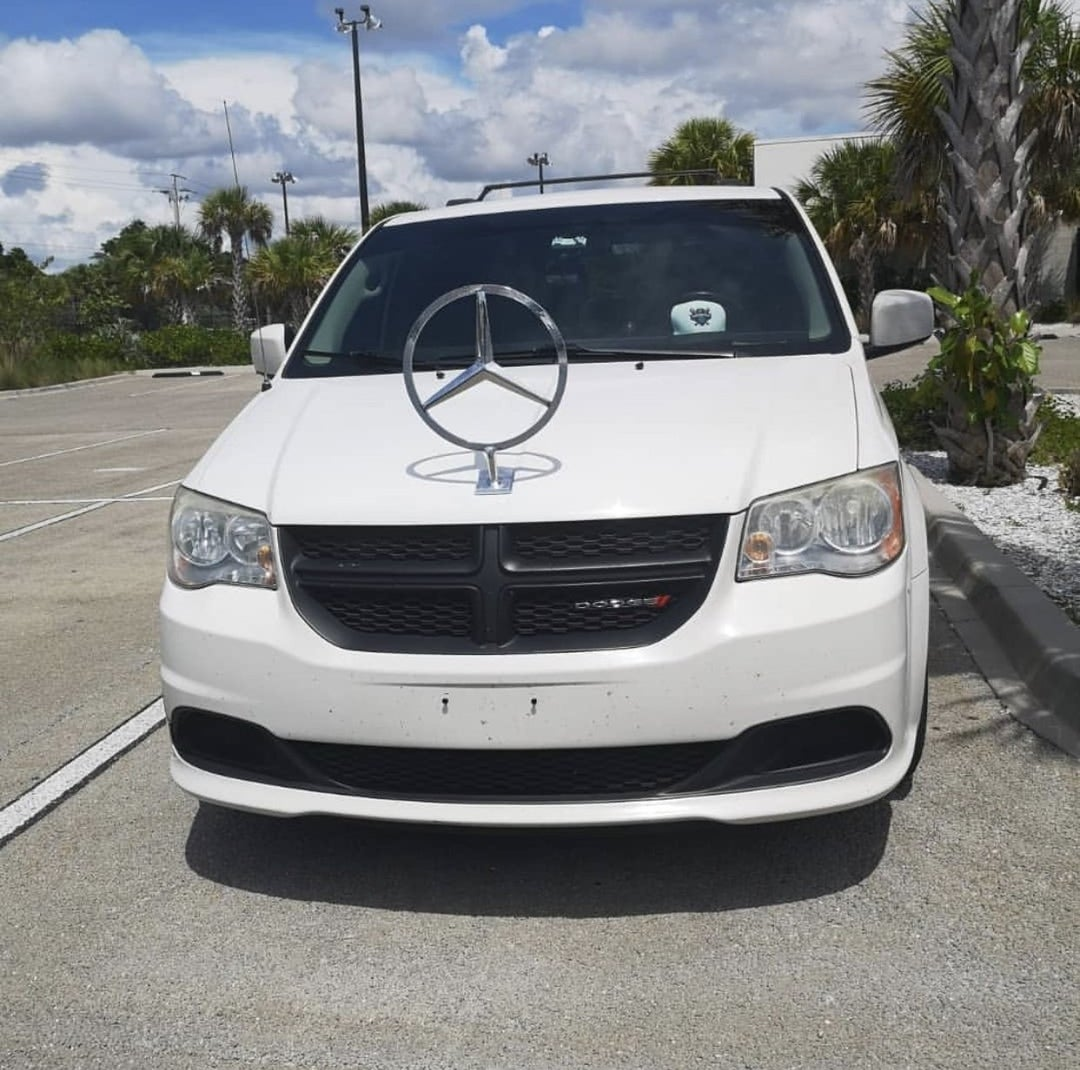 White dodge minivan with mercedes benz emblem
