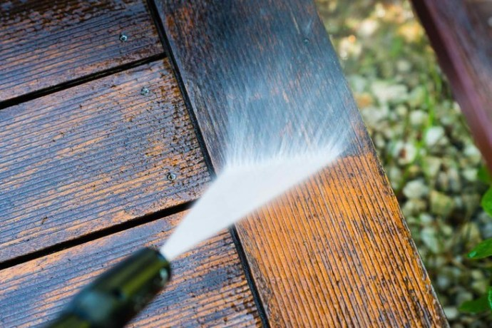 Cleaning the wooden terrace with a high powered pressure washer