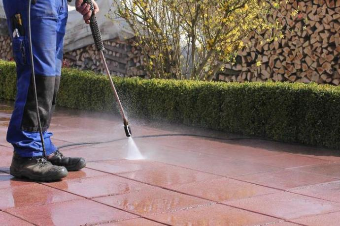Man using a pressure washer to clean the exterior floor of the house