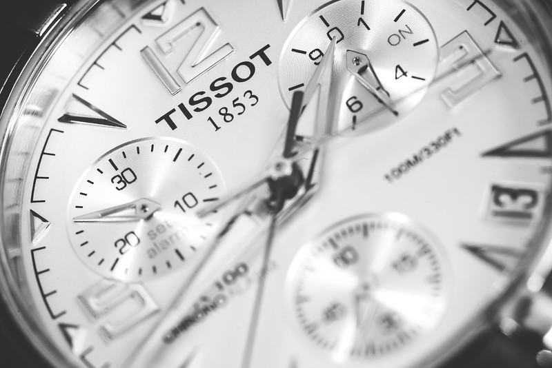 Super close up of the Tissot logo on a silver watch