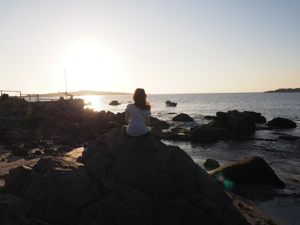 Michelle perched on a rock looking out at the sun set over the ocean in Bahia Inglesa, Atacama Region, Chile