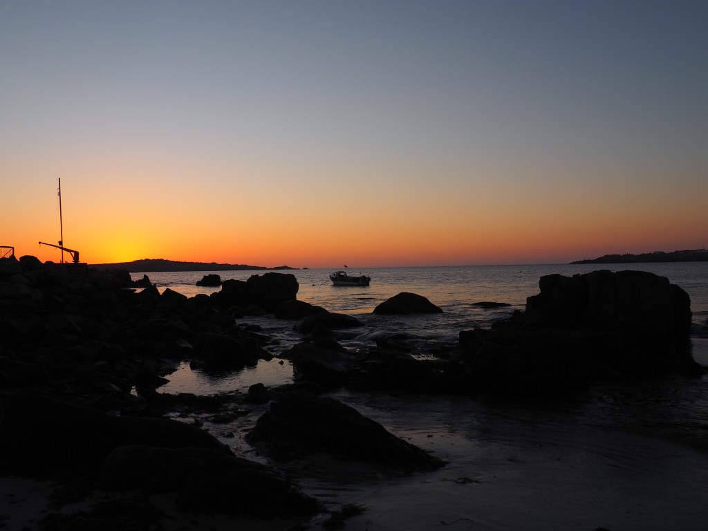 Sun setting over the pacific ocean with boat in the water in Bahia Inglesa, Atacama Region, Chile