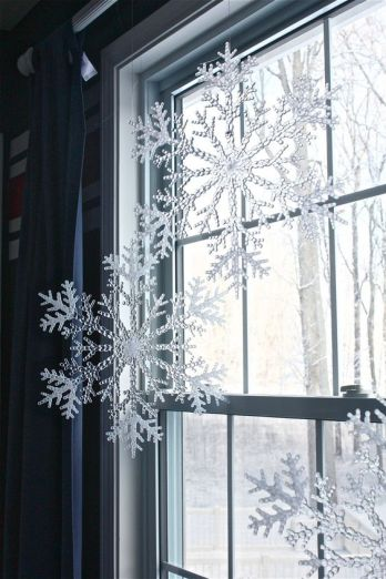 Plastic Snowflakes from Dollar Tree Hung from Curtain Rod with Fishing Wire. Make your home look festive for less this holiday season with easy DIY dollar store Christmas decor ideas. Wreaths, candles, centerpieces, wall art, ornaments, vases, gifts and more!