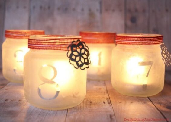 Frosted jars with numbers on them and lighted tea candles on the inside