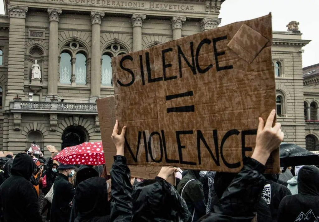 "A protester holding a sign saying ""Silence = Violence"""