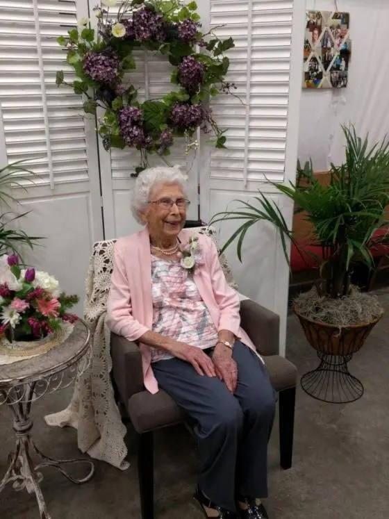 Virginia Tennant, sitting under a wreath.