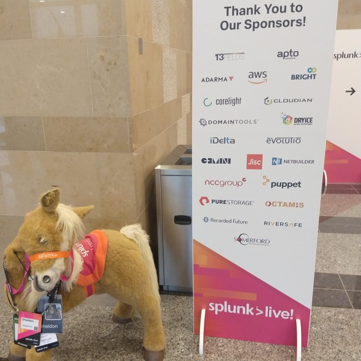 A board reading 'Thank you to our sponsors', including iDelta, stands next to a small toy horse in Splunk livery.