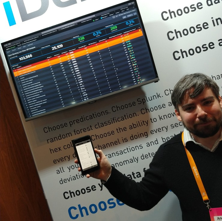 Andrew standing next to a screen showing a splunk dashboard, holding up his phone which contains inputs for the data