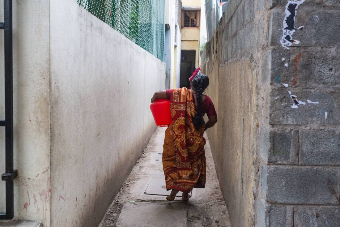 Kannika Arumugam returns home after collecting water from her local pump in Chennai, India. Photo credit: Gayatri Nair