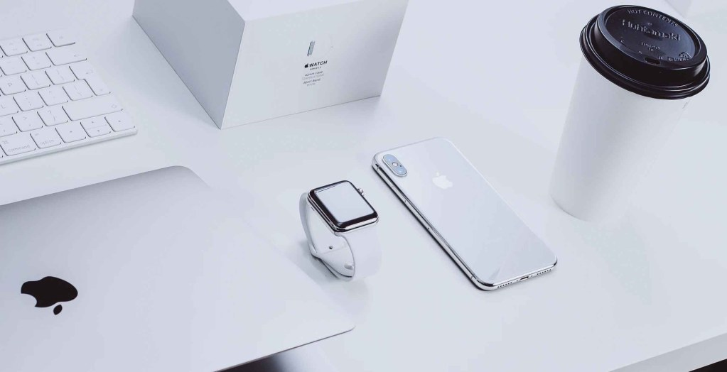 Apple branded products on a desk with a coffee cup