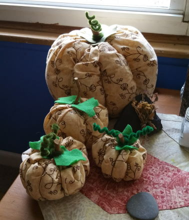 Image shows four fabric pumpkins made from brownish material printed with pumpkins and vines. They sit on a table runner. There is a flat slate grey rock by them.