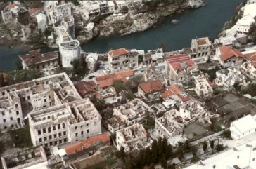 The City of Mostar showing the extensive damage wrought by conflict in the city. The destroyed Old Mostar Bridge is visible in the top left hand corner, the original structure replaced by a temporary pedestrian bridge.