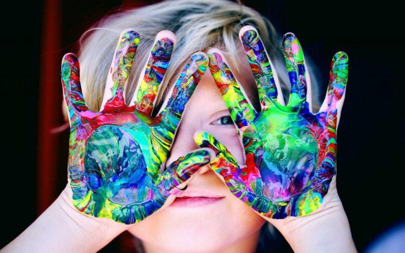 criança com tinta na mão