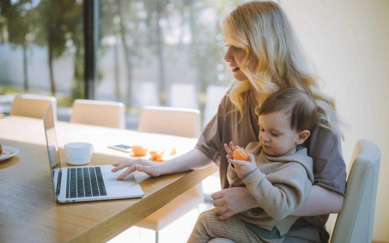 mãe mexendo no computador, com seu filho pequeno no colo