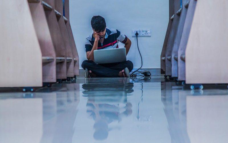 menino estudando na biblioteca, sentado no chão