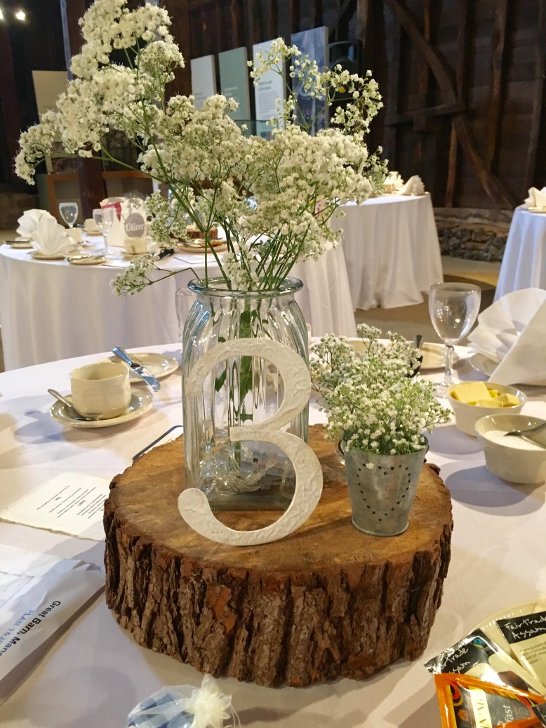 Centrepiece log with table number and jar of flowers