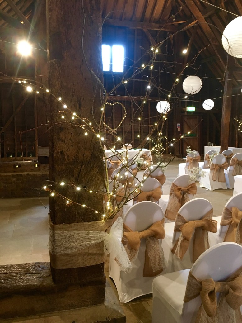 Fairy lights in barn with lace and hessian chair covers rustic barn wedding inspiration