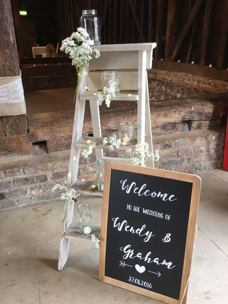 Ladder decorated with jars flowers and personalised chalkboard rustic barn wedding inspiration