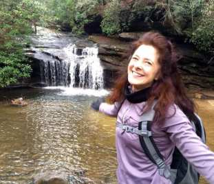 Author in front of waterfall and evergreen trees.