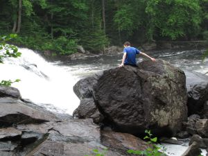 Sitting on a river rock with white water behind