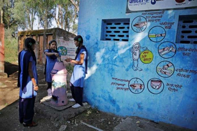 three girls standing around an incinerator as the girl in the middle disposes a menstrual health product into the incinerator. There is a blue wall to their right with wall art about how to safely use a sanitary napkin-menstrual health and hygiene COVID-19