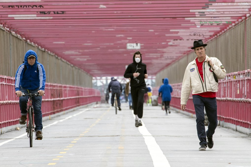 Dans cette photo du lundi 11 mai 2020, un jogger portant un masque facial court entre un motard et un piéton ne portant pas de masque alors qu'ils traversent le pont de Williamsburg à New York.  (Photo AP)