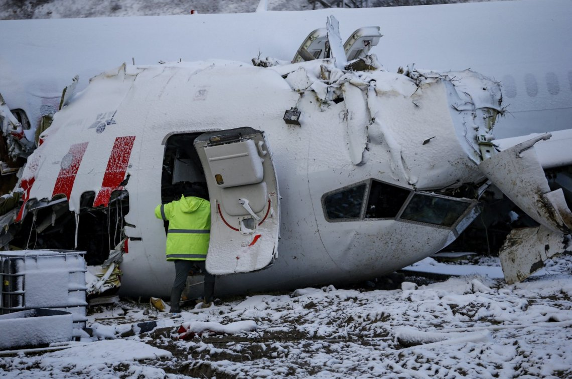 Investigators work at the wreckage of the Pegasus Airlines plane that crash-landed at Sabiha Gökçen Airport, in Istanbul, Turkey, Feb. 8, 2020. (AP Photo)