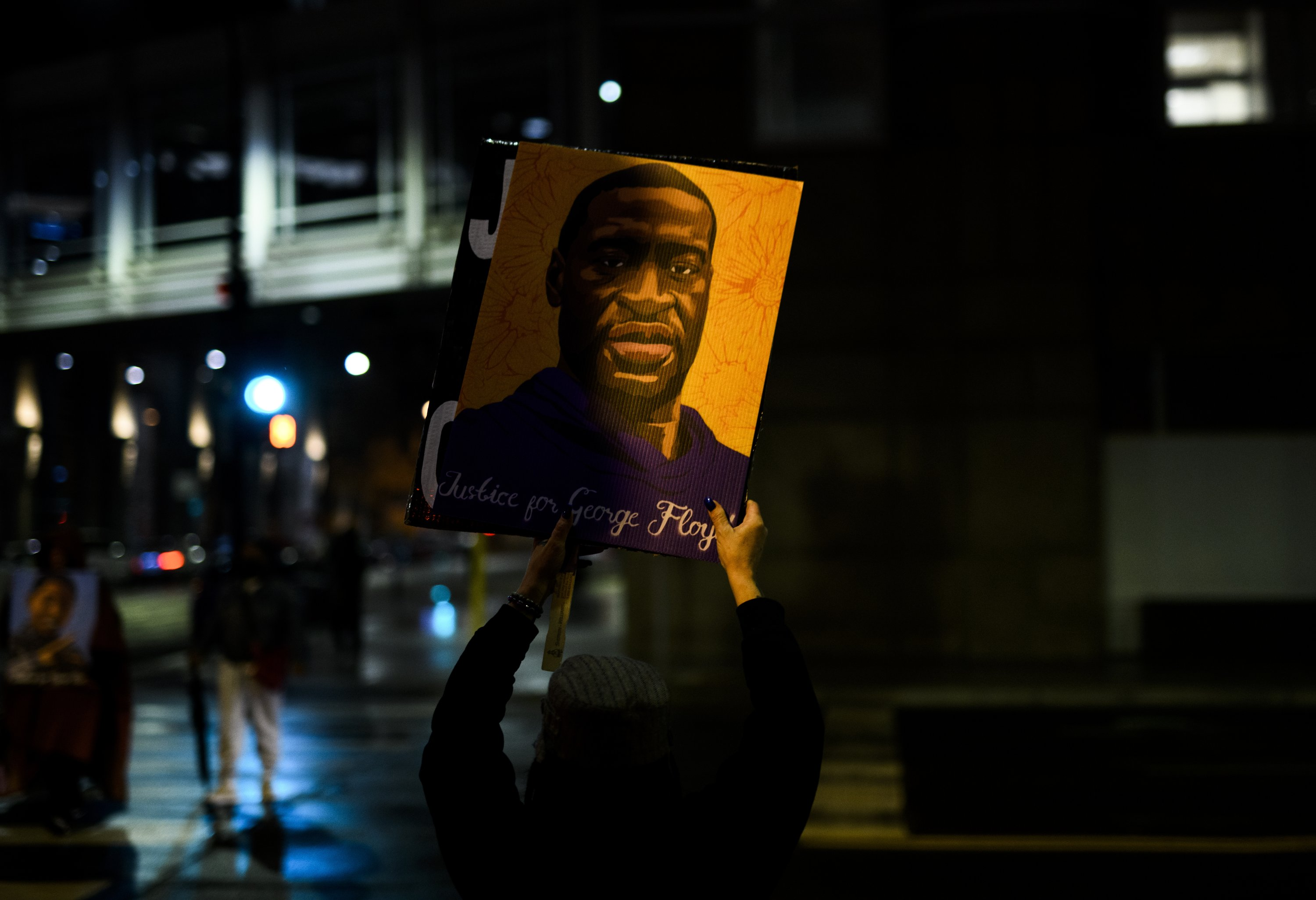 A woman holds up a portrait of George Floyd as people gather outside the Hennepin County Government Center to demand justice for his murder, in Minneapolis, Minnesota, U.S., April 9, 2021. (Photo by Getty Images)