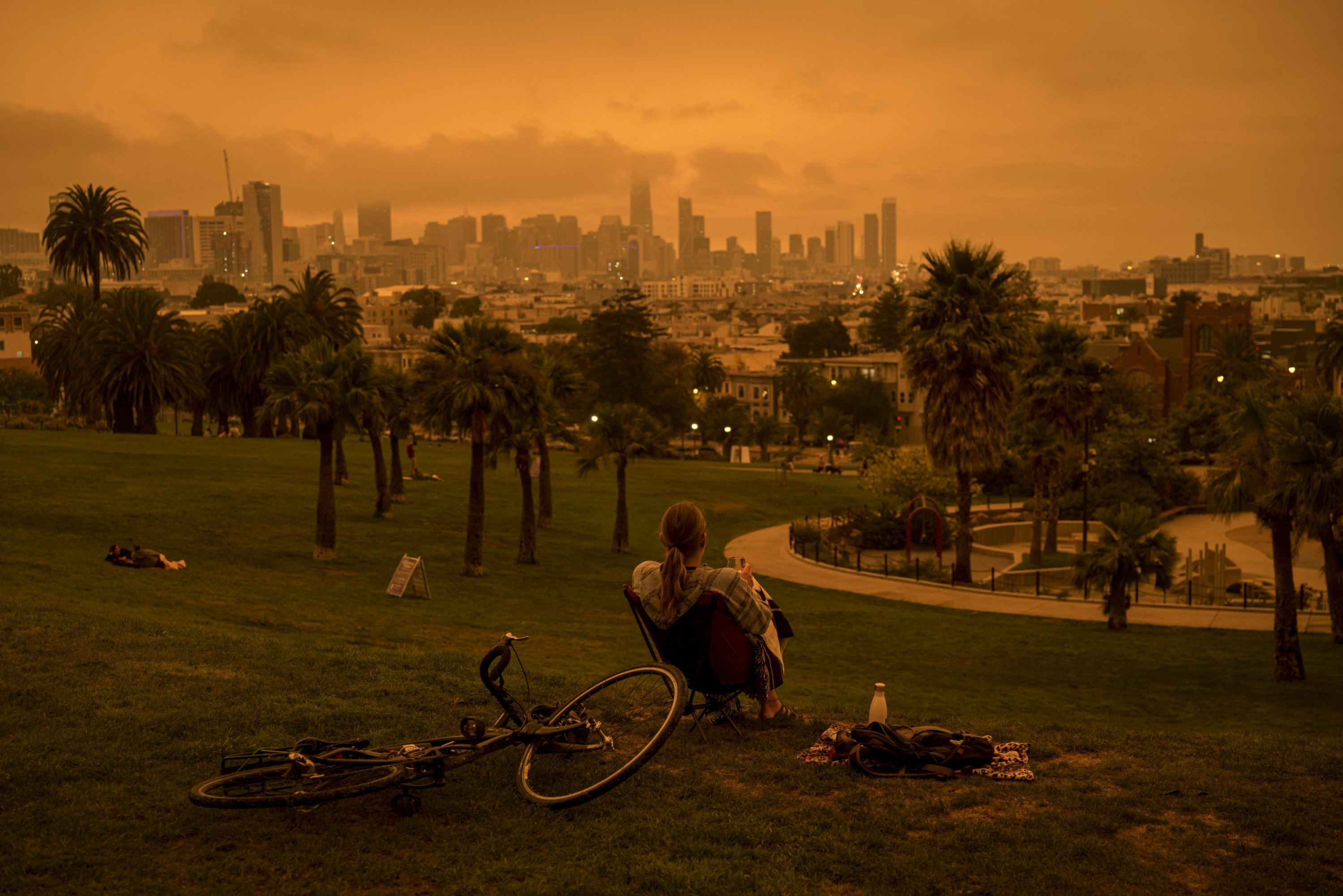 A person sits in Delores Park as smoke and fog hang over the skyline in San Francisco, California, U.S., Sept. 9, 2020. (Photo by Getty Imates)