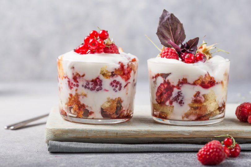 Layered trifle dessert with sponge cake, whipped cream and raspberries in serving glasses on a light background. (Shutterstock Photo)