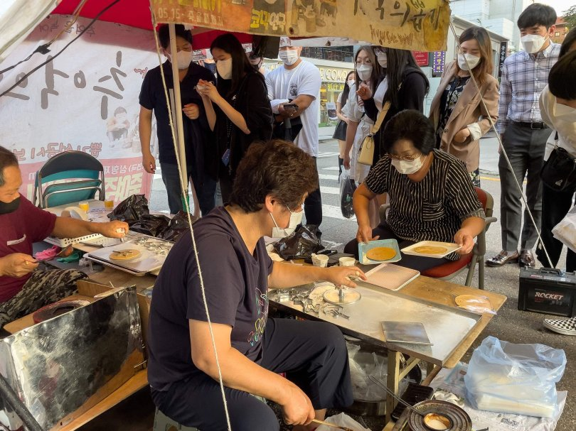 """Customers wait in line as street vendor Jung Jung-soon (C) and her husband Lim Chang-joo (L) sell freshly made dalgonas, a crisp sugar candy featured in the Netflix smash hit series """"Squid Game,"""" in Seoul, South Korea, Oct. 10, 2021. (AFP Photo)"""