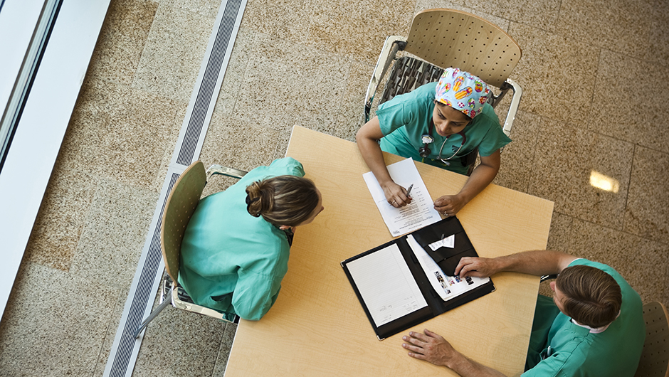 overhead view of 3 Medical Professionals in green scrubs filling out paperwork at a table near a window