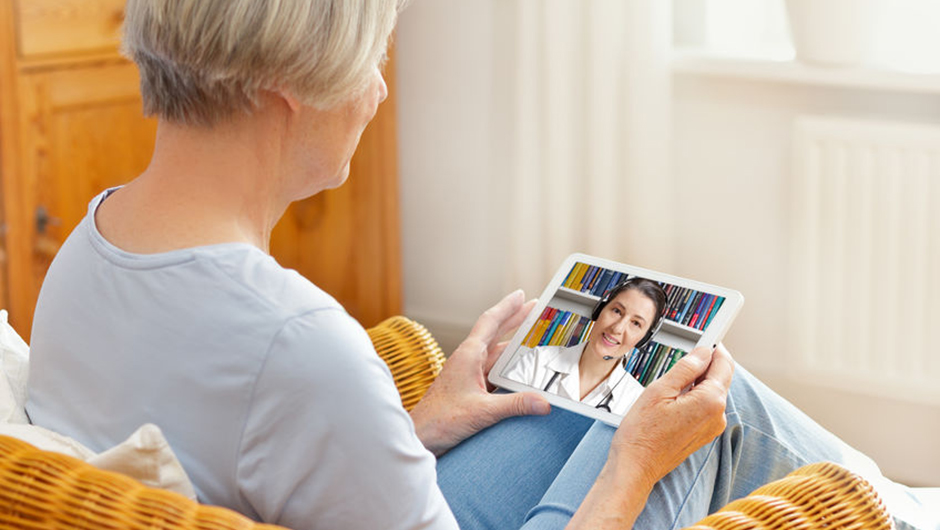 Telemedicine, elderly woman talks to her doctor on a tablet