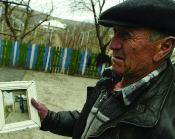 In this photograph taken March 22, 2007, Vasile Dimineti holds a picture of his 24-year-old son, who died a year after selling his kidney. The family lives in the impoverished Moldovan village of Mingir, where about 40 of its 7,000 residents are thought to have sold a kidney. AFP photo/Daniel Mihailescu/Files