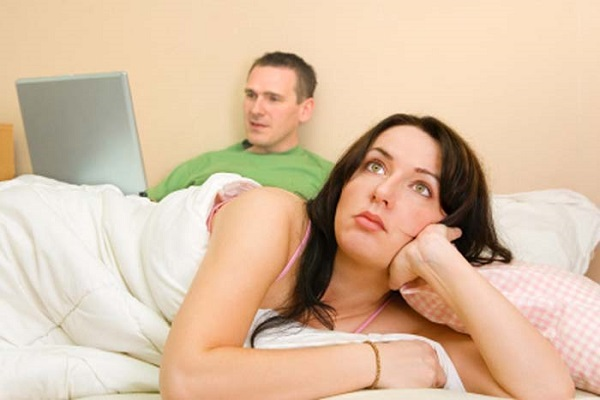 Woman thinking and man using laptop in the background