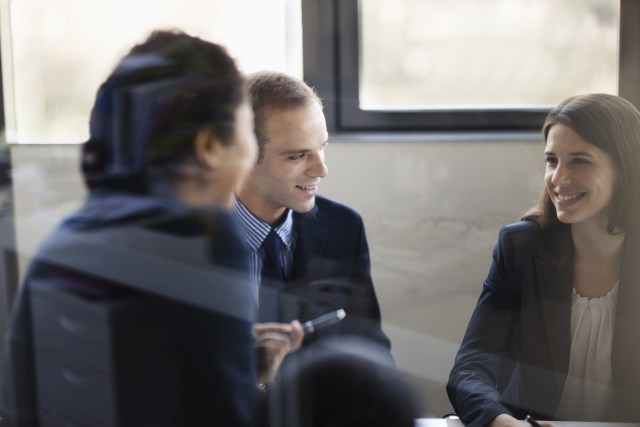 Three business people sitting and discussing at a business meeting