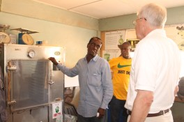 Vincent Afram (left), an official at the Ghana Seed Inspection Unit, demonstrates a seed incubator. The Feed the Future Ghana Agriculture Technology Transfer Project built three new seed labs and installed modern equipment for the Unit.