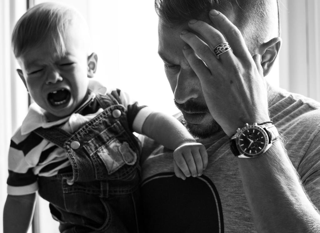 Stressed out father holding crying baby