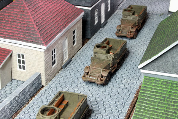 Flames of War British M5 Half Tracks trundle down the cobbled street in Normandy.