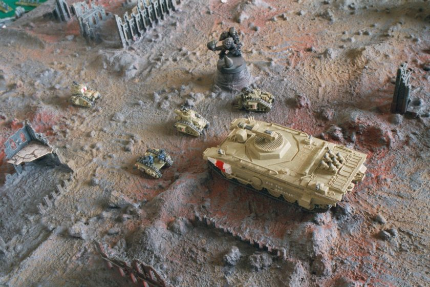 Variant Imperial Leviathan escorted by Leman Russ tanks rumble slowly through the ruins of an Imperial city.