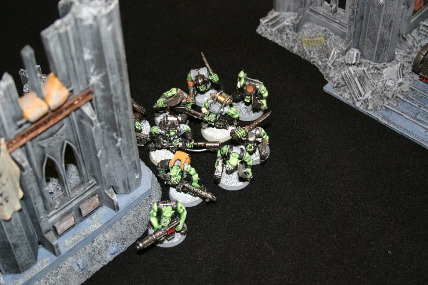 Ork Shooty Boyz advance through the ruins of an Imperial City during a Warhammer 40000 Cities of Death game.
