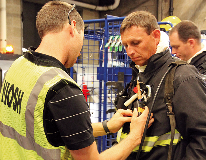 Attaching air monitoring equipment to turnout gear for measuring chemicals during the fire.