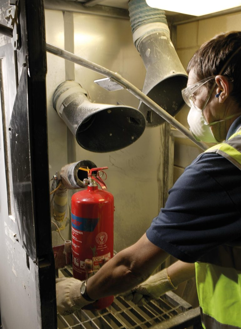 A certified professional oversees the recycling of a used fire extinguisher.