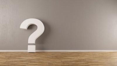 FAQ Fragezeichen lehnt an einer Wand als Konzept für Zweifel